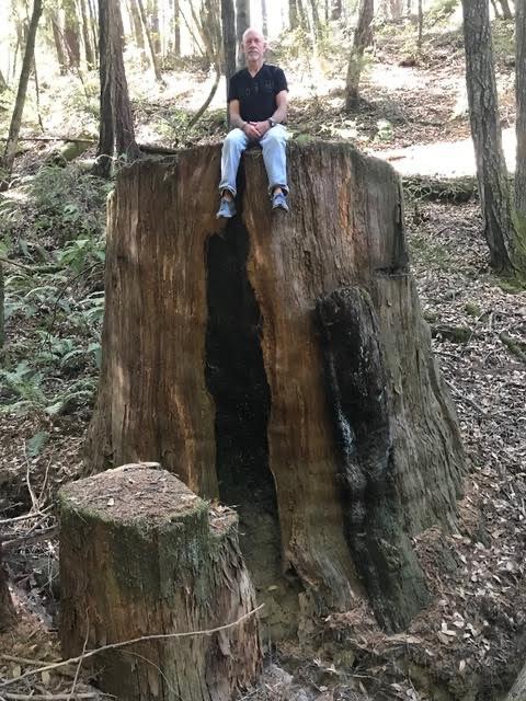 Chris Poehlmann sitting on a large stump