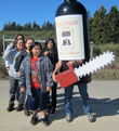 Chainsaw Wine human sized bottle with students from Kashia Elementary School
